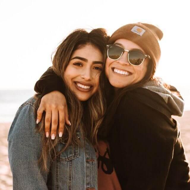 woman wearing sunglasses after Lasik hugging her daughter
