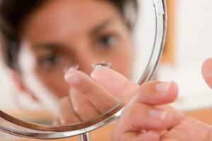 Kid holding up contact lens in mirror - Eye Doctor - Paramus NJ