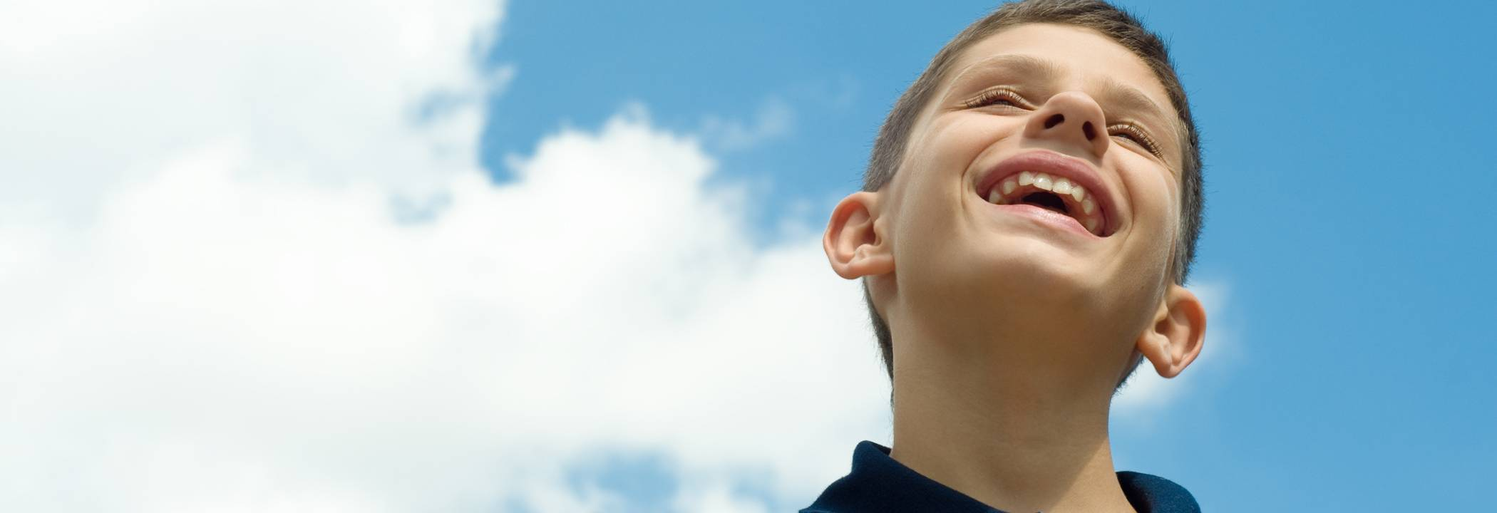 white_boy_smiling_blue_sky_on_rt_CROP