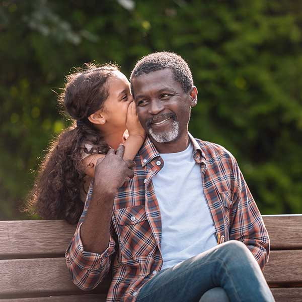 older Black man with his daughter at the park smiling at eye clinic near you