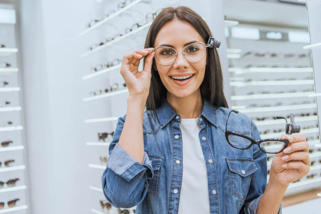 cheerful young woman choosing eyeglasses and looking at camera in ophthalmic shop