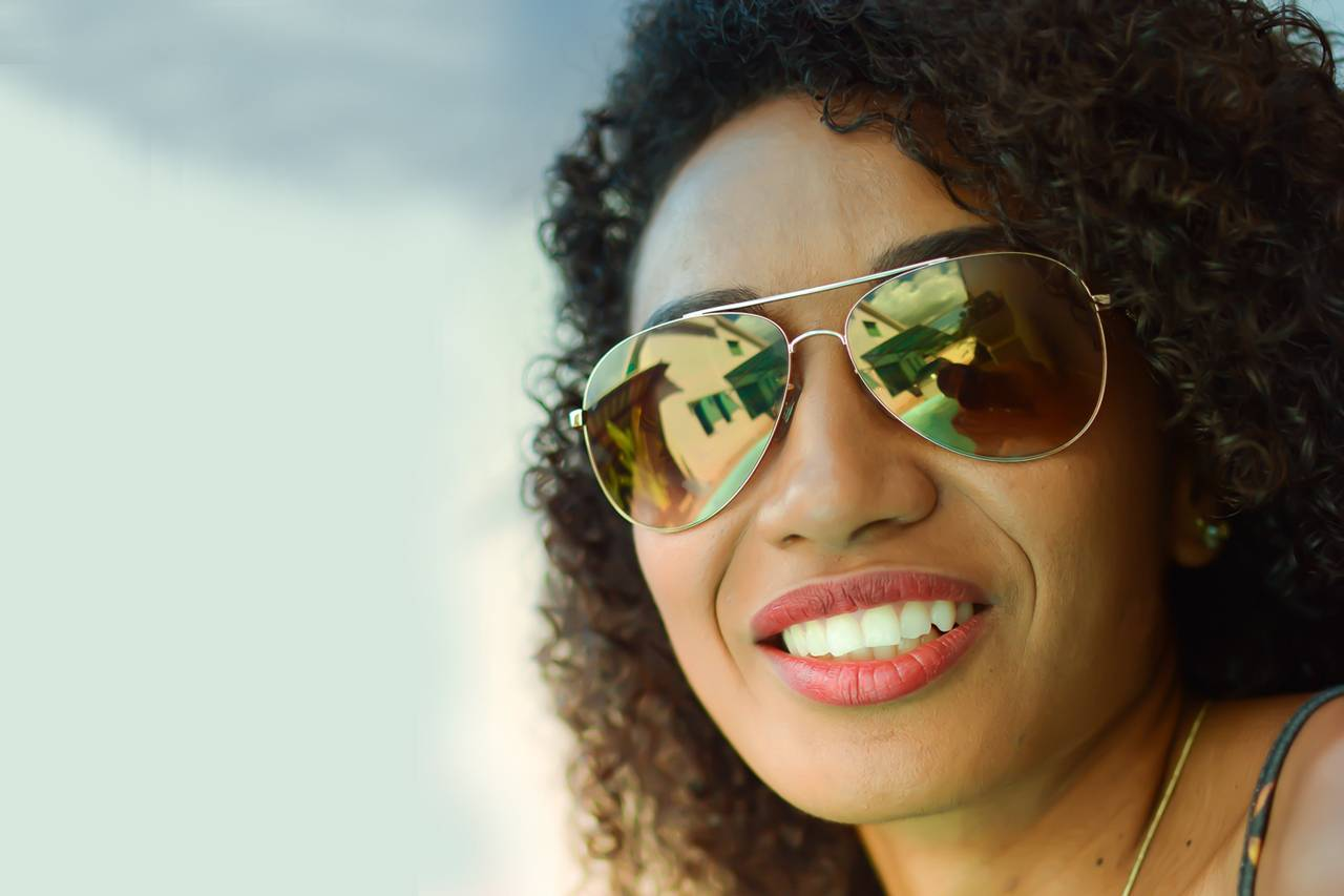 Woman-Smiling-Sunglasses-Sky-1280x853