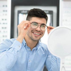 Optical Shop. Female Optician In White Coat Holding Glasses, Hel