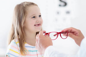 Child At Eye Sight Test. Little Kid Selecting Glasses At Opticia