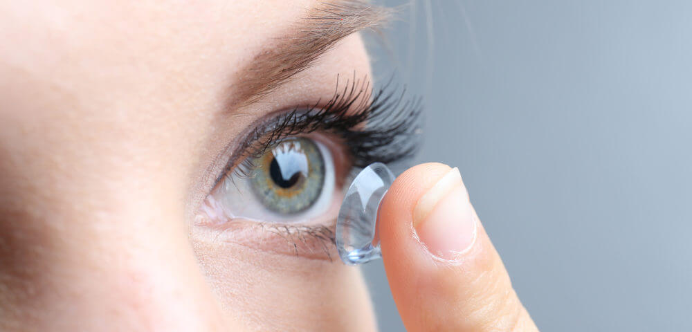 Contact lens exams—Lady putting contact lens on eye to replace picture of smiling man