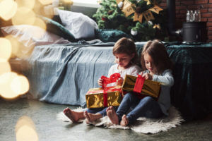 Pull on those red things to open. Christmas holidays with gifts for these two kids that sitting indoors in the nice room near the bed