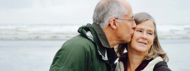 senior man with glaucoma, kissing wife