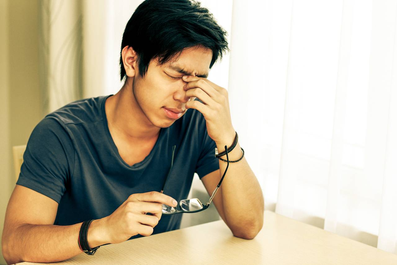 Young man with eyeglasses suffering from dry eyes
