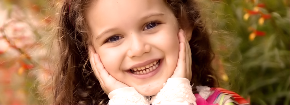 child with blue eyes holding her face slide