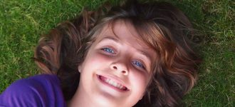 A child laying on the grass, Eye Care in Hartsdale, NY