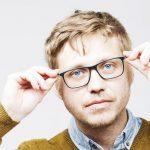 Eye doctor, man holding his eyeglasses in Hartsdale, NY