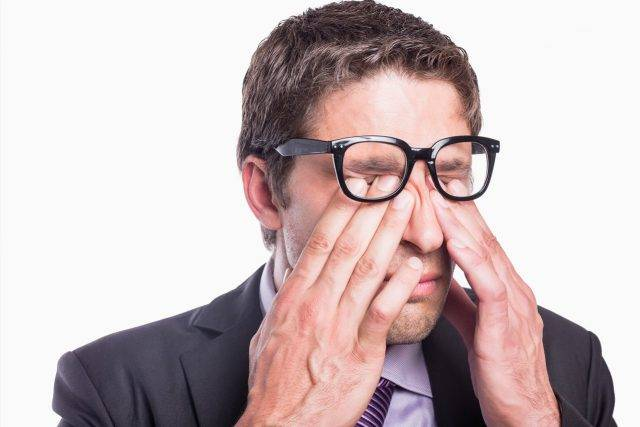 businessman rubbing dry eyes