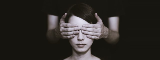 Woman's eyes being covered from behind