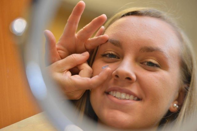 girl trying on contacts in mirror 640x427