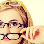Eye doctor, woman wearing multiple pairs of glasses in Madison, WI