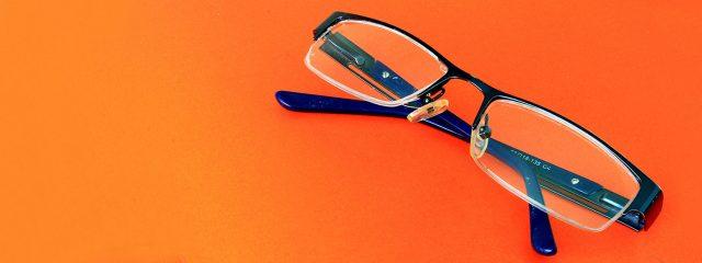 Optometrist, pair of eyeglasses on orange surface