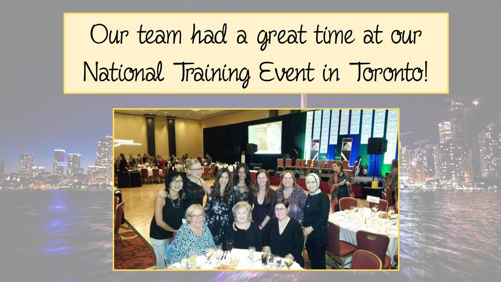 Our team had a great time at our National Training Event in Toronto! Photo of team sitting and standing at table and smiling at National Training Event.
