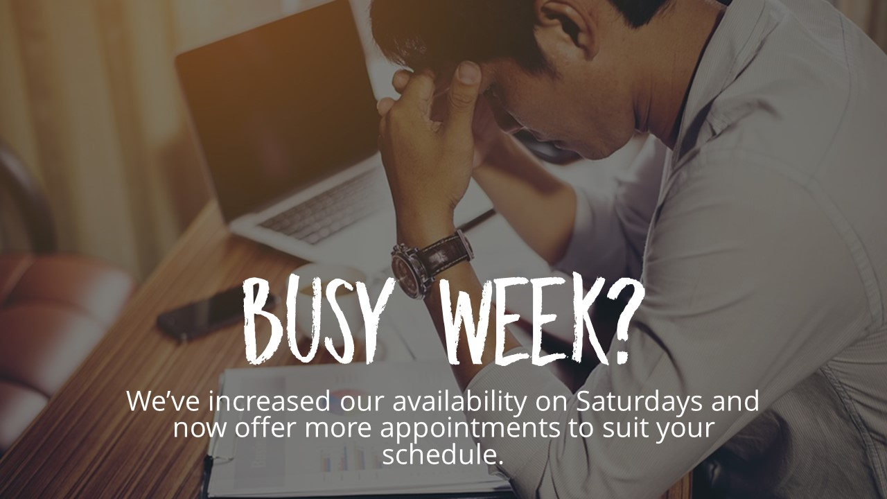 Background photo is a person looking stressed while sitting at a laptop. Text says Busy Week? We've increased our availability on Saturdays and now offer more appointments to suit your schedule.