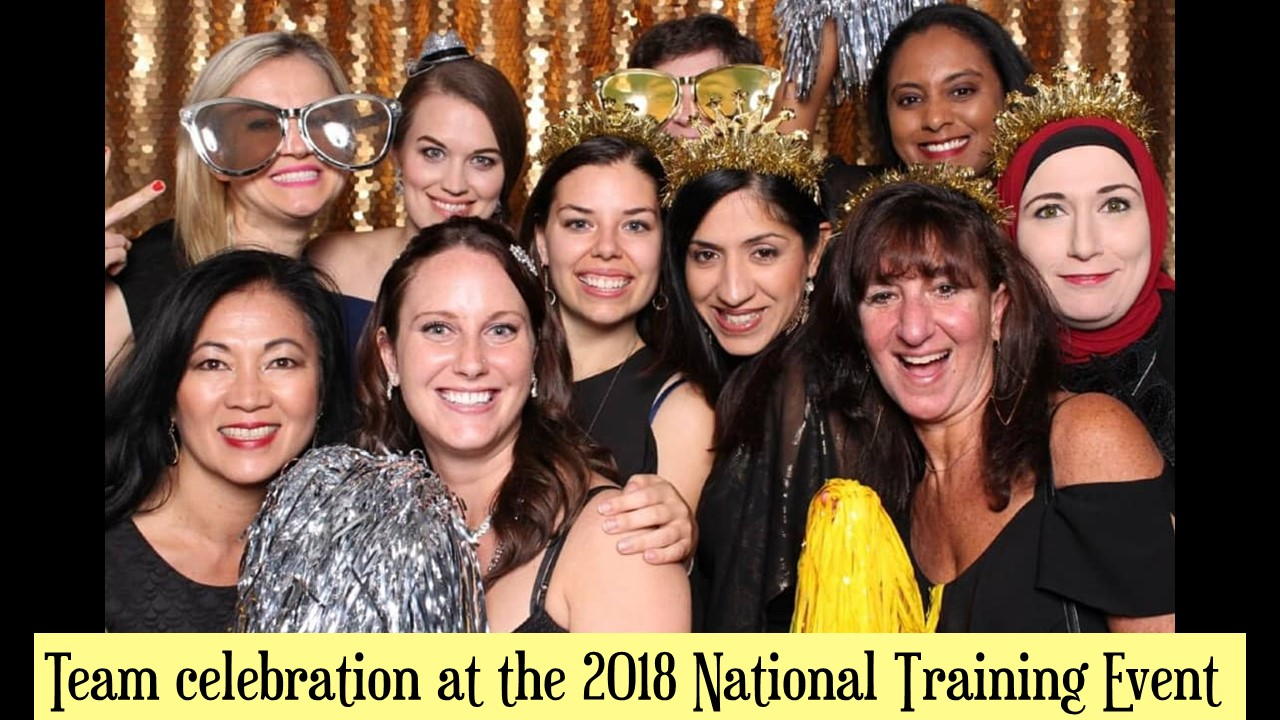Photograph of the Milton Family Eye Care team wearing silly hats, oversized glasses and pom-poms in a photo booth. Team celebration at the 2018 Training Event.