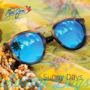 Photograph of sunglasses with blue mirrored lenses on a yellow and green fabric background with small sea shells. Superimposed text reads Maui Jim Sunny Days.