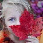 optometrsit, child covering one eye with leaf in Huntington, Lake Grove, New York