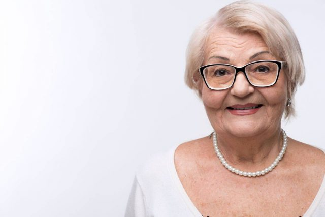 senior woman with glasses for keratoconus treatment with eye doctor
