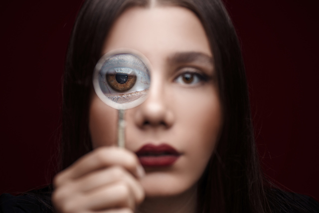 Woman experiencing dry eye, holding magnifying glass