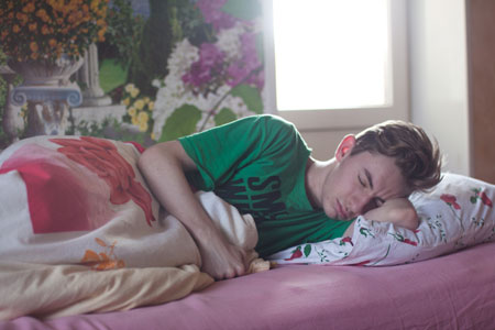 man wearing green printed crew neck shirt while sleeping