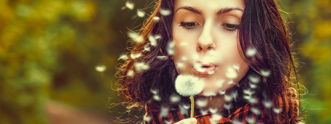 Eye doctor, woman with eye allergies blowing a dandelion in Toronto, ON
