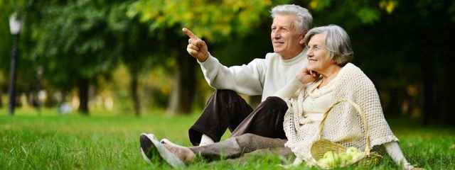 senior couple sitting in park with macular degeneration