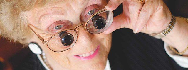 Eye doctor, senior woman wearing low vision eyeglasses in Oak Brook, IL