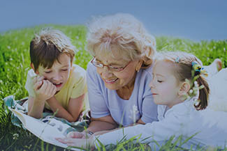 Optometrist, Grandmother Reading Book To Grandchildren Outdoors in Oak Brook,IL