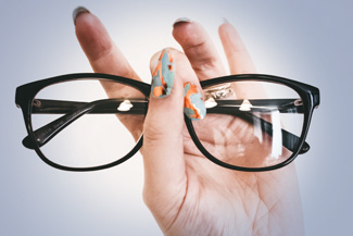 Eye care, woman is holding eyeglass with Essilor lenses in Oak brook,IL