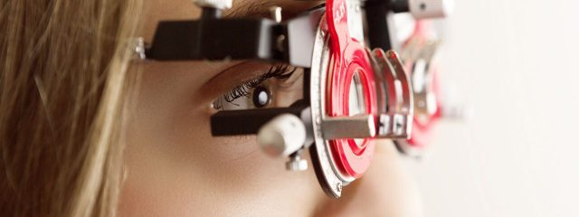 Eye doctor, woman using a phoropter in Carrollton, TX