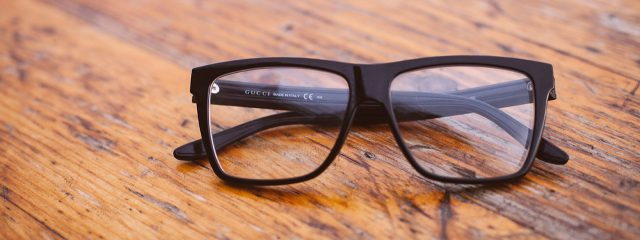 eye doctor, black glasses on wood table in Cypress, TX