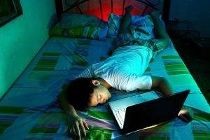 boy on bed in the dark with computer, Blue Light, Optometrist, Plano TX