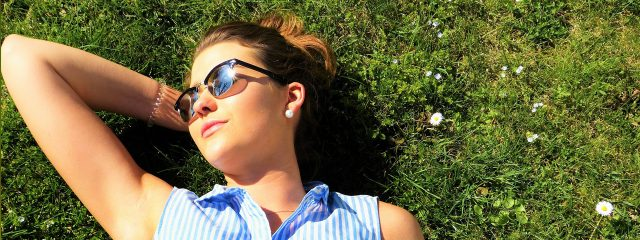 Woman Sunglasses Laying on Grass - eye exam, plano, TX