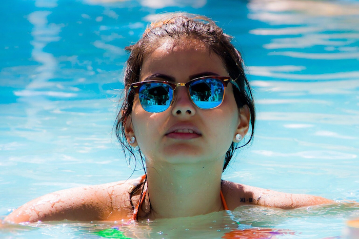 Woman in Pool Wearing Sunglasses 700×466
