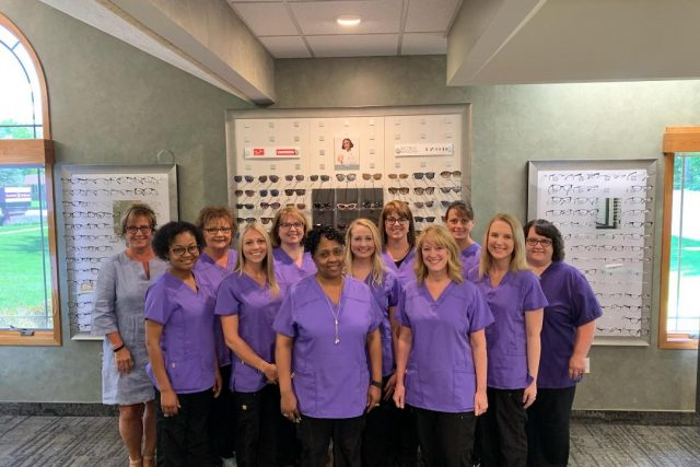 Our Eye Care Staff in front of our optical display in Saginaw, MI