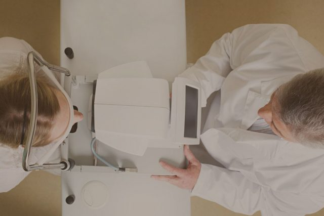 Eye doctor using eye care technology with patient