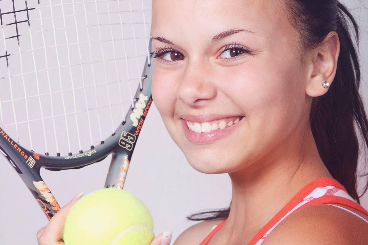 Eye doctor, girl smiling, holding a tennis racket in Nesconset, NY