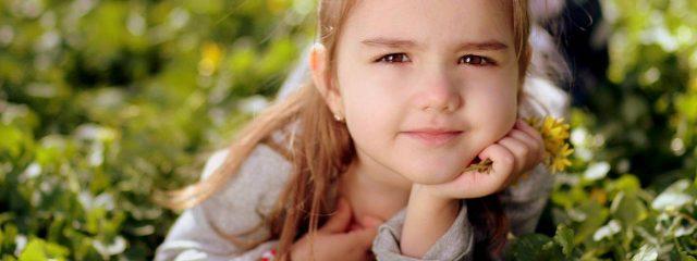 Eye doctor, little girl sitting on the grass in London, Ontario