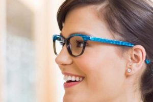 Woman wearing blue eyeglasses, smiling