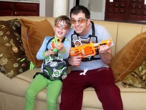 man and boy wearing protective goggles and playing with nerf guns