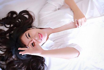aisian lady with finger circling eye smiling_440x293