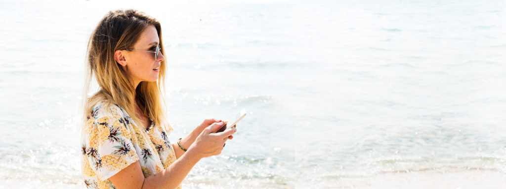 Woman Sunglasses Beach Texting 1280x480 1024x384