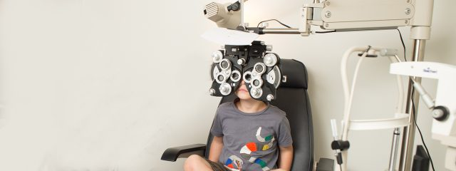 Eye doctor, little boy using a phoropter in Danbury & Stamford, CT
