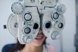 Eye doctor, woman wearing a phoropter in Bourbonnais, IL