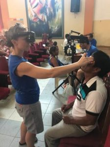 Volunteer Eye Doctor from Colorado Springs CO, giving eye exam to patient in Zorritos, Peru