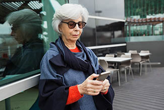 Eye care, Serious Focused Lady In Sunglasses Using Mobile Phone. Grey Hair in Akron, OH